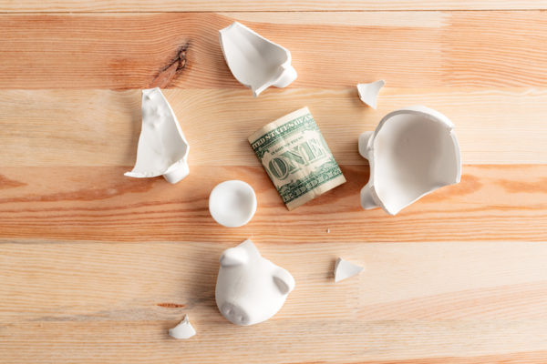 Dollars in broken piggy coin bank, money savings in home budget and finances concept