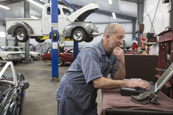 A senior caucasian male car mechanic working on his laptop computer in his classic car repair shop.