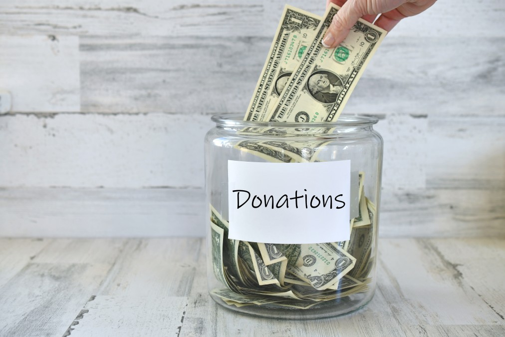 putting-money-into-a-jar-to-collect-funds-for-a-good-cause-charity-relief-fund-for-a-local-or-global_t20_lLZNdZ