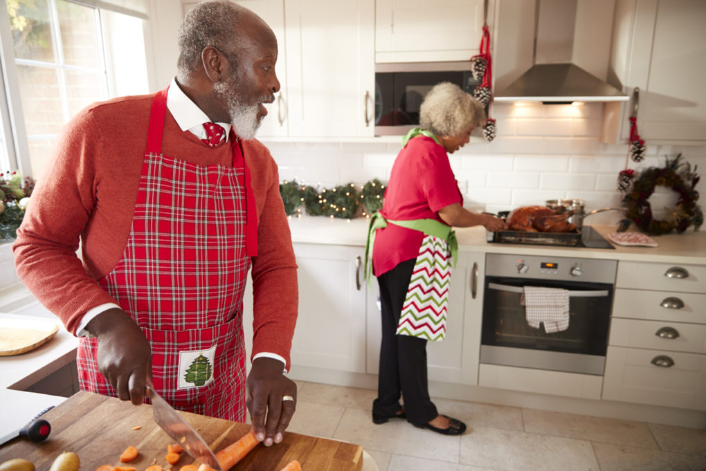 Mature couple preparing Christmas dinner, man chopping vegetables in the foreground, turning to his partner who is preparing the turkey.